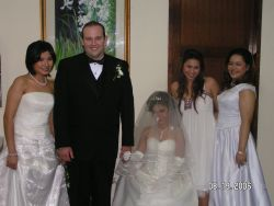 Flower girl in veil holds groom's hand while his bride unveiled holds the other