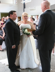 A groom stands next to his bride as the pastor reads a blessing over them
