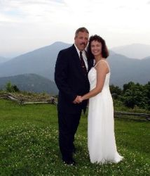 Gorgeous hills in the background as a newly wedded Christian couple smile and pose together