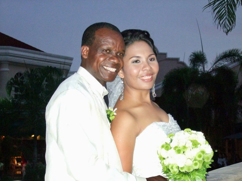 A proud Black Christian man smiles while holding his new Asian bride