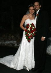 A super happy man smiles as her stands next to his beautiful bride, who holds her wedding bouquet