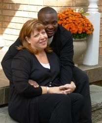 A man lovingly hugs a woman while sitting on the stairs with flowers in the background