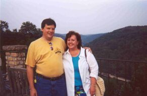 Christian couple hug with hills in the background