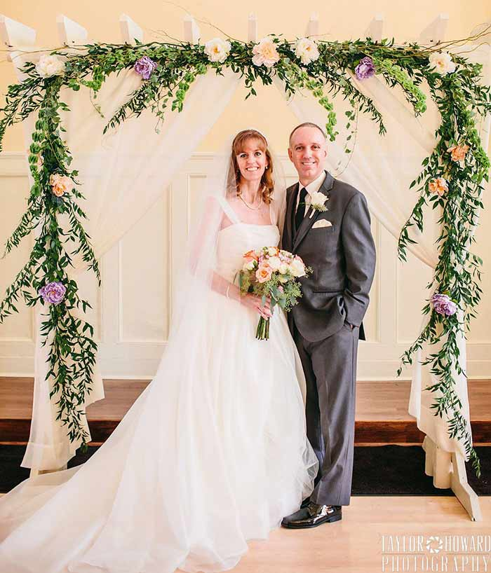 A couple smile under an arch with flowers