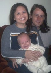 Christian couple try to soothe crying baby while posing together and smiling