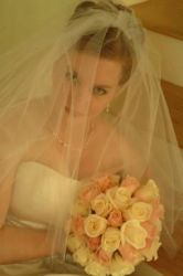 A pretty bride in veil holds her flowers