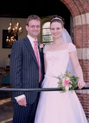 Overjoyed American Christian woman smiles on her wedding day standing next to her Dutch Christian husband