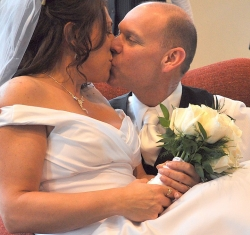 A bride overcome with joy leaps into her husband's arms and kisses him while still holding her bouquet