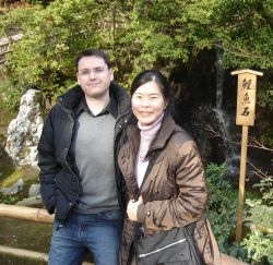 Canadian man meets a Japanese Christian woman. They both stand on a bridge on a cool but sunny day