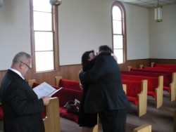 A pastor shyly looks away as a newly married couple wholeheartedly embrace
