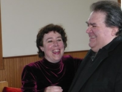 A man giggles while his wife looks at him and laughs