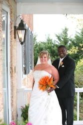 A very happy couple pose together on porch and smile