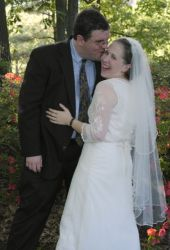 A man sneaks a kiss as his bride laughs joyfully