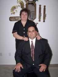 A proud man is seated and smiling as his wife stands behind and hugs him
