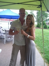 A stunning woman in a grey dress poses next to an athletic man outside