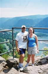 A Christian couple go on a hiking date and pose together at a mountain lookout