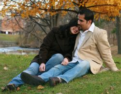 Touching photo of a woman lying her head on her man's shoulder in a park in Autumn
