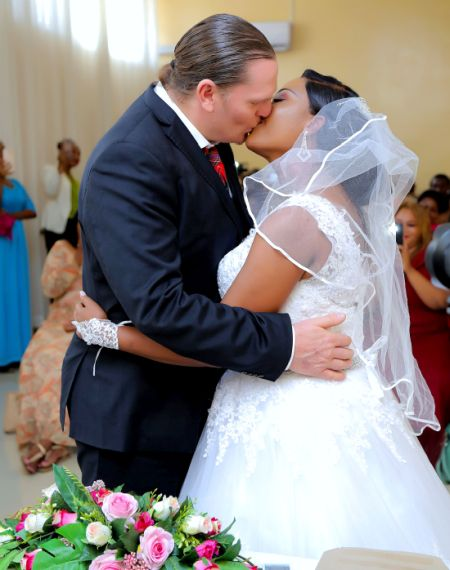 Interracial Christian couple kiss after marrying