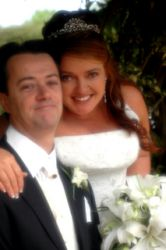 An excited Australian Christian bride smiles broadly with her arm around her new husband