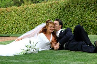 Groom whispers in his wife's ear as they lie on the grass for a photo