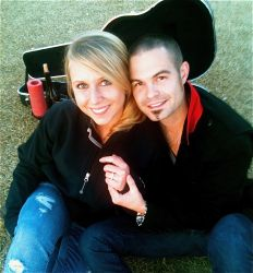 Newly engaged Texas Christian woman shows off her engagement ring while her Texas fiance holds her hand and smiles proudly