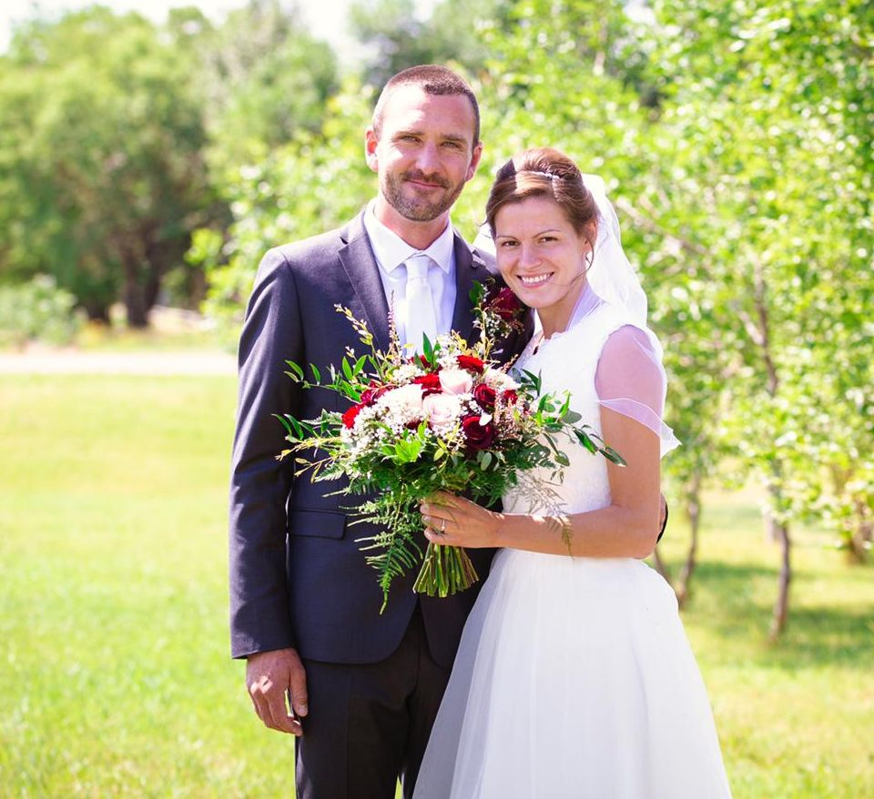 Young Manitoba Christian singles just married, holding bouquet while posing outdoors