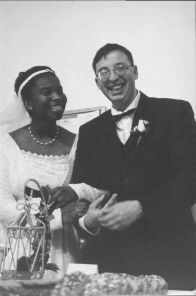 A very happy White Christian man smiles and holds on tight to his smiling new bride