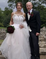 English Christian couple with French connection pose together proudly on their wedding day
