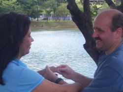 A very happy man puts an engagement ring on a woman while standing near a beach