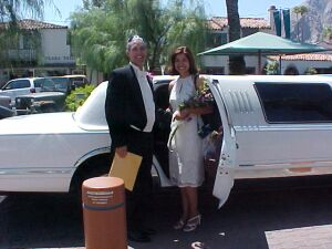 Christian couple recently married laugh as they step into limousine