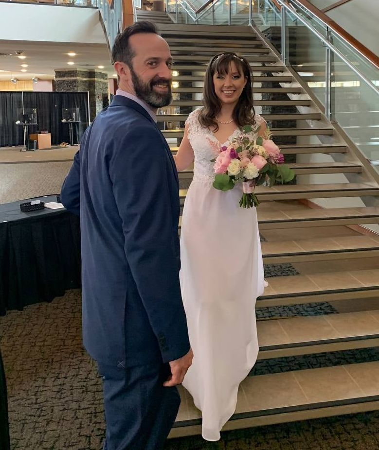 A Christian man smiles as his beautiful bride walks down the stairs
