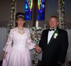 A Christian woman in a beautiful pink wedding dress holds hands with her handsome new husband