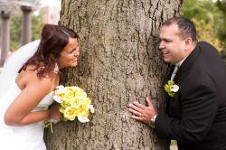 a joyful Christian couple play tag around a tree