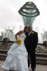A couple smile excitedly outdoors just after marrying