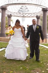 Finally married, a couple walks hand in hand at their outdoor wedding