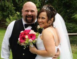 No happier groom! Laughing groom hugs his beautiful wife who smiles