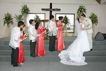 Wedding couples look at bride and groom kissing at the altar