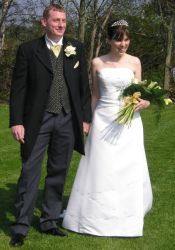 A beautiful bride looks very happy as she stands next to her new husband