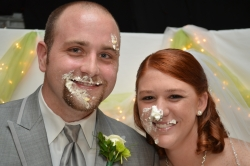 A young Christian couple laugh with wedding cake all over their faces