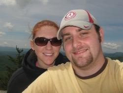 A woman in sunglasses stands behind a man in a baseball cap while on a hike