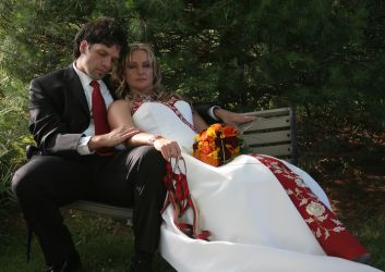 Exhausted bride rests in her husband's arms as he caresses her arm