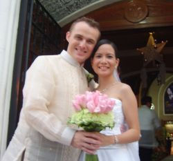 Interracial Christian couple smile and hold bride's wedding bouquet