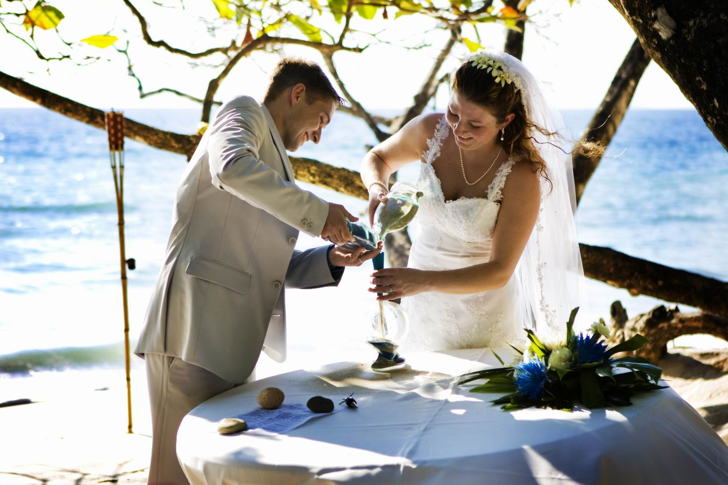 Bride and groom pour sand into marriage bottle at beach wedding