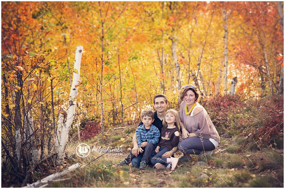 A beautiful Christian family sit and hug in an Autumn forest