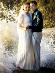 Great shot of newly married couple posing with waves crashing behind them