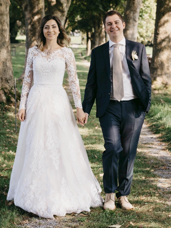 Swiss Christian couple holding hands in tree-lined garden