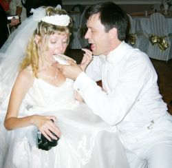 Newlyweds laugh as they try to feed each other wedding cake