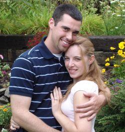 Proposal in rose garden as man hugs his beautiful fiancee