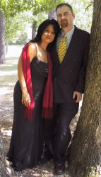 A Christian couple pose together against a tree and look very pleased