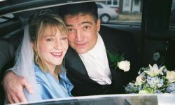 A man leans over his wife to close car window after marrying